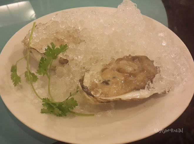 Fresh chilled oyster accompanied with sliced lime